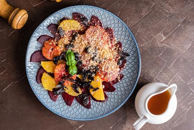 Salat aus roten orangen, zuckerrüben, orangen, gemahlenen mandeln, getrockneten pflaumen, honigsauce.