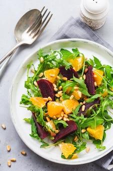 Salat aus rucola, gebackener roter bete, orange und roten zwiebeln mit gewürzen und pinienkernen in einem weißen teller. olivenöl und zutaten auf grauem steintisch. selektiver fokus.