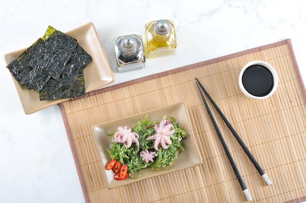 Salat aus seekohl-chuka, tintenfisch, sojasauce, grünkohl-chips