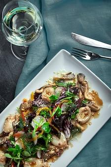 Salat aus tintenfisch, pilzen und gemüse. der blick von oben. textfreiraum.