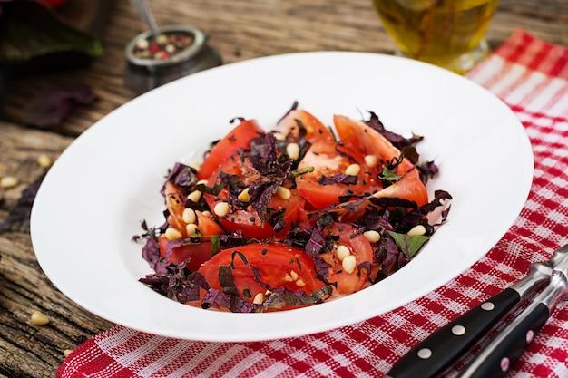 Salat aus tomaten mit einem violetten basilikum und pinienkernen. veganes essen. italienisches essen.
