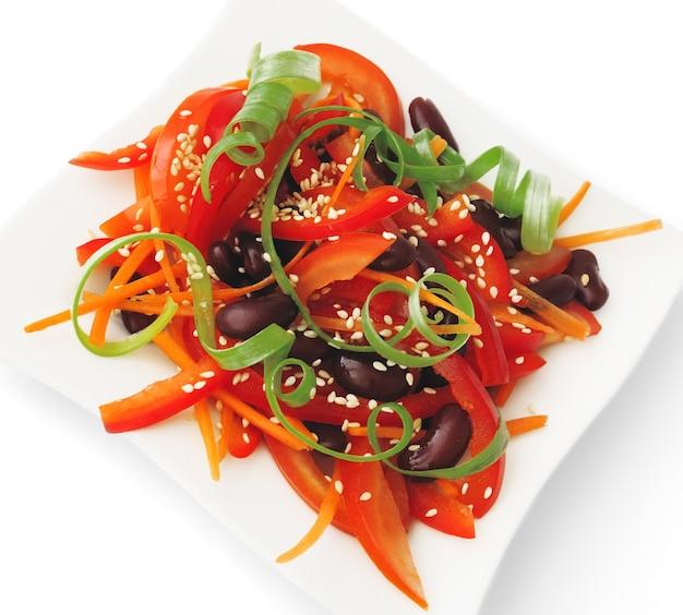 Salat aus tomaten, paprika, roten bohnen, karotten mit sesam