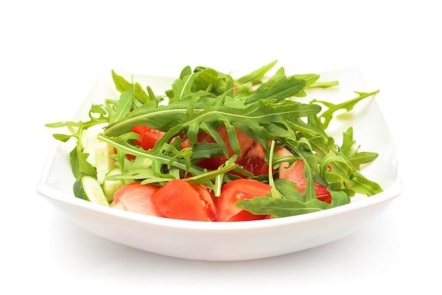 Salat aus tomaten, rucola, pfeffer, olivenöl auf weißem teller