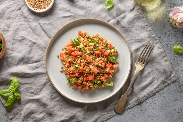 Salat aus vollkorngetreide mit gemüse auf grauem tisch.