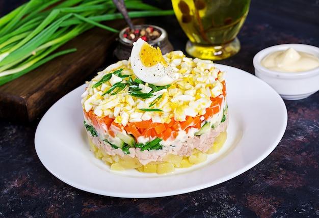 Salat der dorschleber mit eiern, gurken, kartoffeln, frühlingszwiebeln und karotten in einer platte.