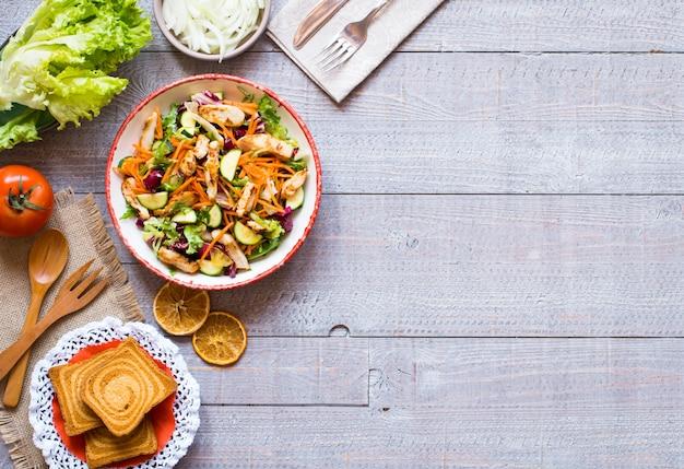 Salat der hühnerbrust mit zucchini- und kirschtomaten, auf einem hölzernen hintergrund
