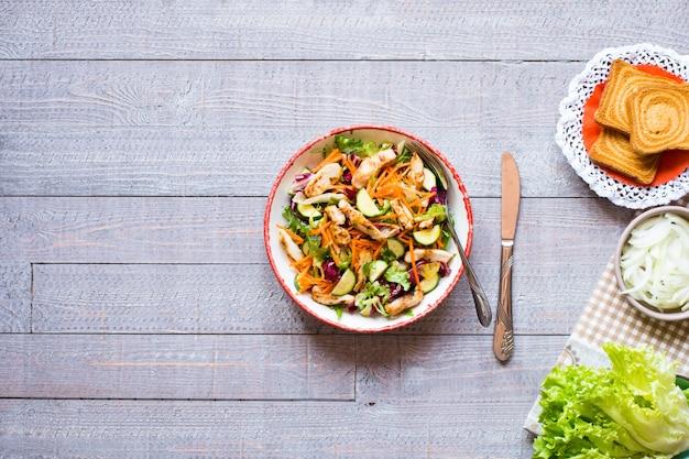 Salat der hühnerbrust mit zucchini und kirschtomaten, auf einem hölzernen hintergrund