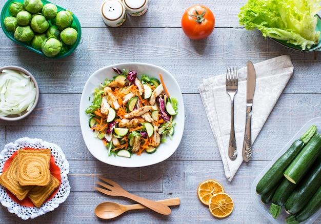 Salat der hühnerbrust mit zucchini- und kirschtomaten, auf einer holzoberfläche