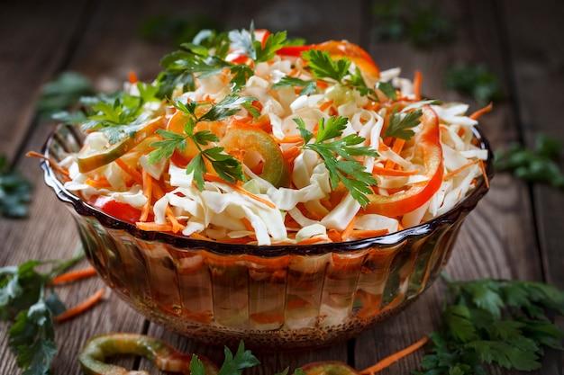 Salat des frischen kohls, des roten grünen pfeffers, der karotte und der petersilie auf einem natürlichen holztisch nahaufnahme