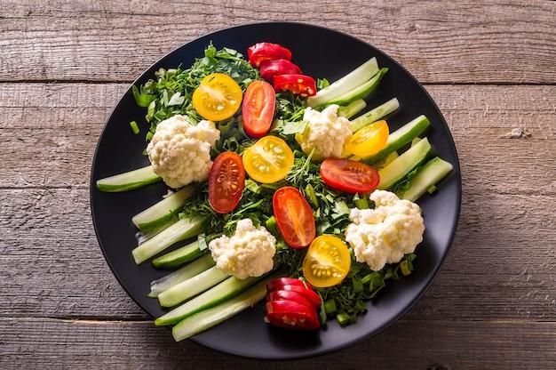 Salat des frischgemüses auf schwarzblech über hölzernem, abschluss oben