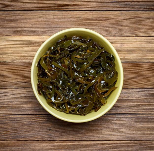 Salat des seekohls und des indischen sesams auf einer draufsichtnahaufnahme des braunen hölzernen hintergrundes