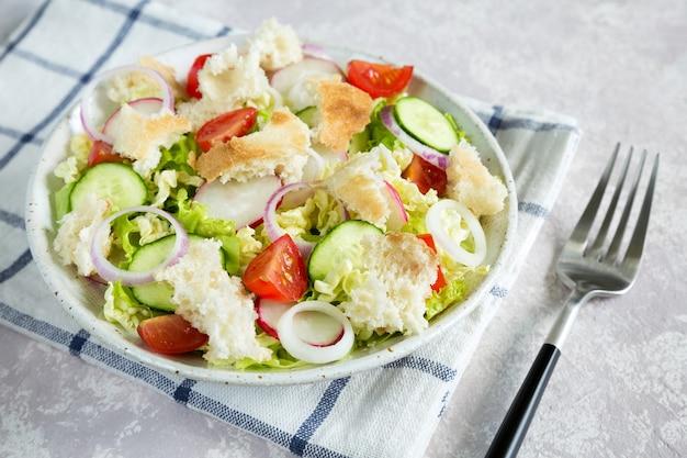 Salat fattoush nahaufnahme mit geröstetem fladenbrot und gemüse in der weißen platte auf der serviette mit gabel.