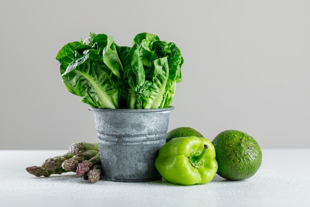 Salat in einem mini-eimer mit spargel, pfeffer, avocado auf weißem und grauem tisch