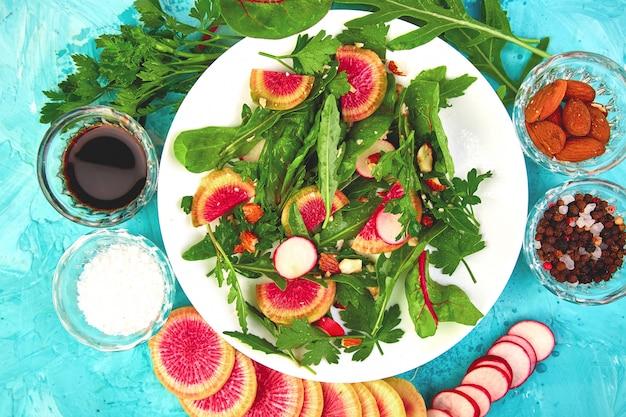 Salat in weißen teller um zutaten mix blatt rettich, salat, mangold, petersilie, rucola, mandel, salz, lecker, balsamico, pfeffer. gesunde ernährung. klares essen. vegan. flach liegen. kopieren sie platz.