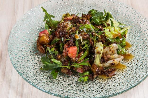 Salat mit arugula in der glasplatte auf hellem hölzernem hintergrund in einem restaurant