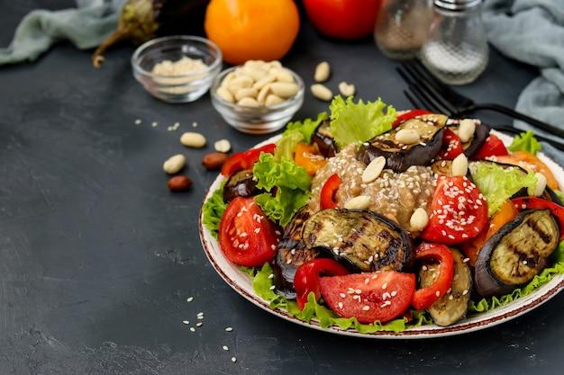 Salat mit auberginen, tomaten, paprika, salat, sesam und erdnüssen auf einem teller auf dunklem tisch, horizontale ausrichtung, kopierraum, nahaufnahme