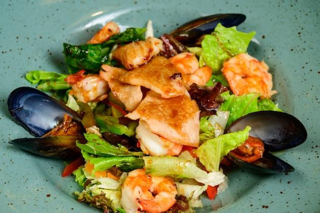 Salat mit austern, garnelen und gemüse auf blauem teller auf hölzernem hintergrund, draufsicht