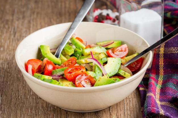 Salat mit avocado, tomate, roter zwiebel, geschmackvollem aperitif, traditionellem mittagessen, gesundem lebensmittel