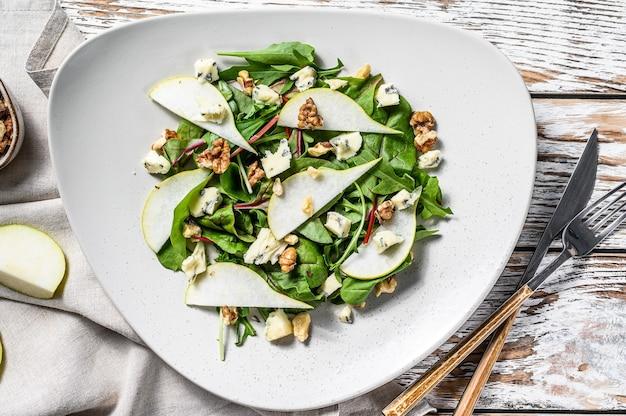 Salat mit blauschimmelkäse, birnen, nüssen, mangold und rucola. weißer hintergrund. draufsicht.