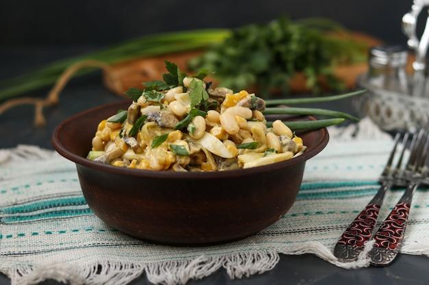 Salat mit bohnen, mais, eiern und champignons in einer braunen schüssel