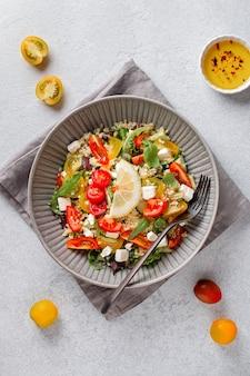 Salat mit bulgur, kirschtomaten, feta-käse und grünen kräutern auf betontischplatte. taboulé-salat aus dem nahen osten, ansicht von oben, vertikales bild