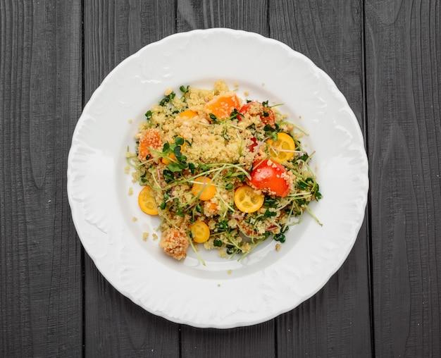 Salat mit bulgur und gemüse, tabouleh, auf dunklem holz. tönung.