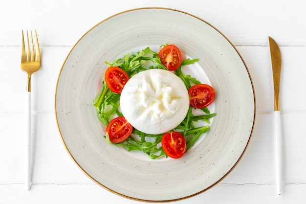 Salat mit burrata-käse und kirschtomaten auf weißem holz