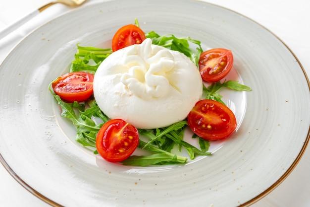 Salat mit burrata-käse und kirschtomaten auf weißem holzhintergrund