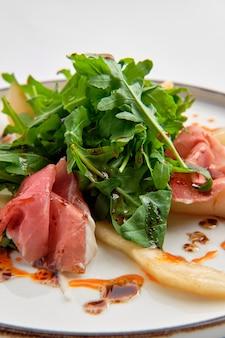 Salat mit dem jamon, birne und arugula getrennt auf weiß