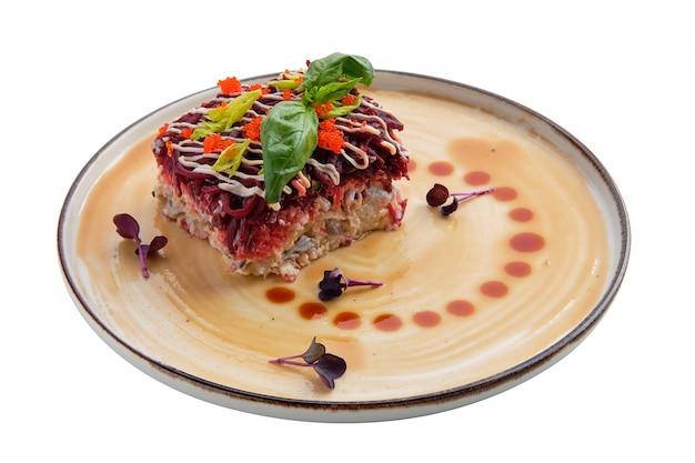 Salat mit den heringen, roter rübe, kartoffel, karotte und kaviar lokalisiert auf weiß