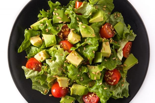 Salat mit der avocado, kopfsalat, tomate, leinsamen lokalisiert auf weißem hintergrund. ansicht von oben
