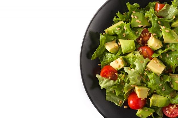 Salat mit der avocado, kopfsalat, tomate, leinsamen lokalisiert auf weißem hintergrund. kopieren sie platz