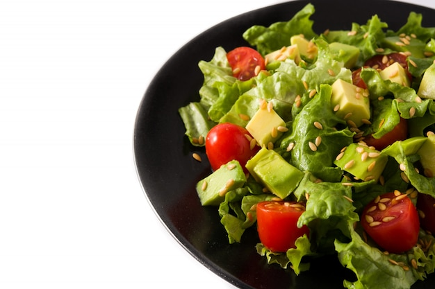 Salat mit der avocado, kopfsalat, tomate, leinsamen lokalisiert auf weißem hintergrund