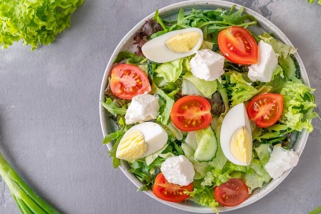 Salat mit eiern, tomaten, käse und salat.