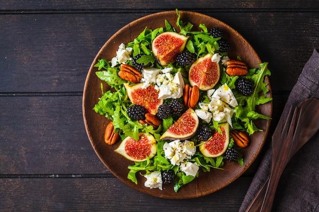 Salat mit feigen, feta-käse und brombeeren in einem holzteller auf dunkel