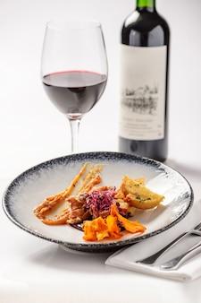 Salat mit fleisch, croutons und süßkartoffelchips mit einem glas rotwein