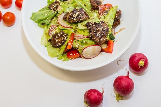 Salat mit fleisch, gemüse, paprika und tomaten.