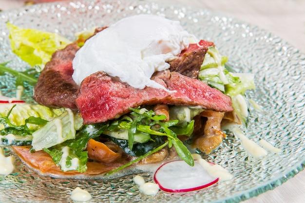 Salat mit fleisch in der glasplatte auf leuchtpult in einem restaurant