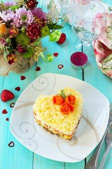 Salat mit fleisch, pilzen, käse und gemüse auf dem festlichen tisch am valentinstag.
