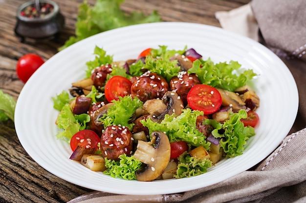 Salat mit fleischbällchen, auberginen, champignons und tomaten im asiatischen stil. gesundes essen.