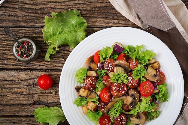 Salat mit fleischbällchen, auberginen, pilzen und tomaten nach asiatischer art.