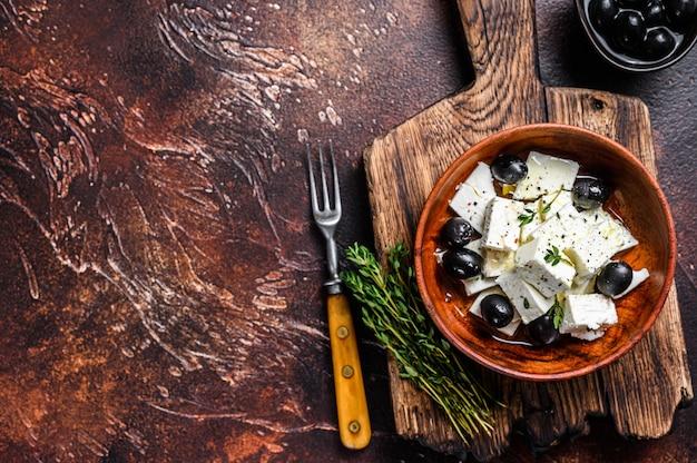 Salat mit frischem fetakäse, thymian und oliven. dunkler hintergrund.
