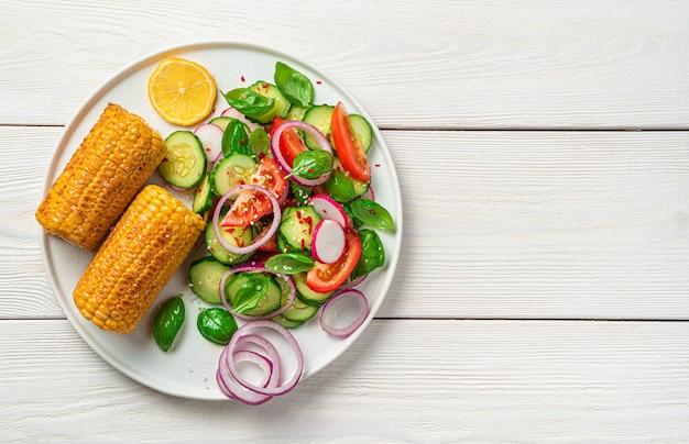 Salat mit frischem gemüse, tomaten, gurken und rettich, gewürzt mit sesam und gewürzen auf einem weißen holztisch mit platz zum kopieren