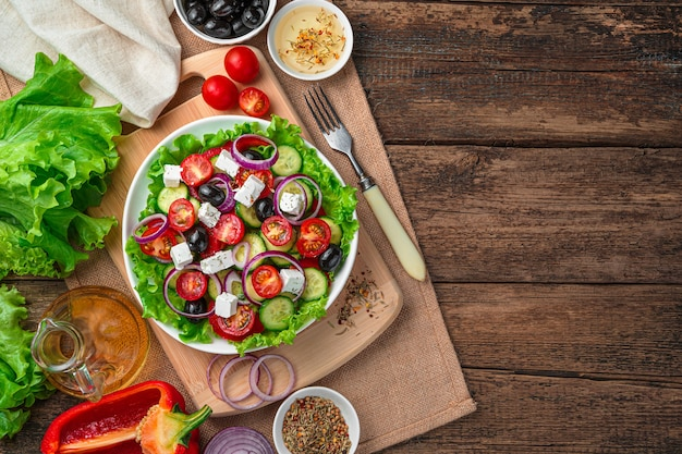Salat mit frischem gemüse und kräutern auf braunem grund. draufsicht mit kopierraum.