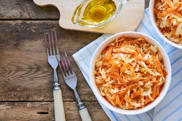 Salat mit frischem kohl, karotten und olivenöl in einer weißen schüssel auf einem holztisch