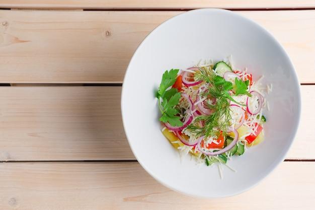 Salat mit frischem paprika, gurke, roter zwiebel, salzkartoffel und käse. ansicht von oben.