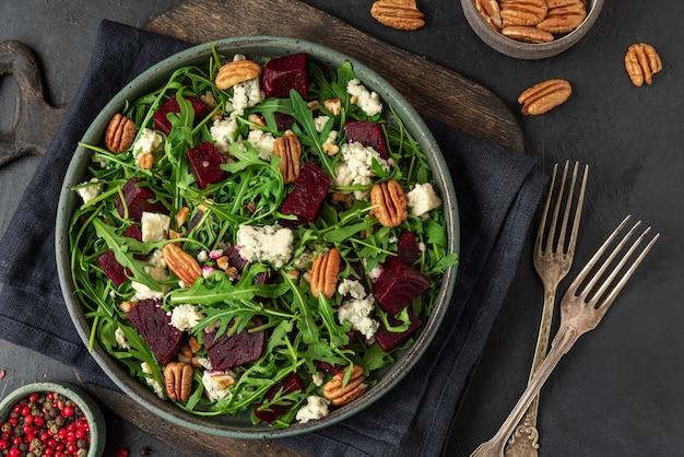 Salat mit frischem rucola, roter bete, gorgonzola und pekannüssen in einem teller mit gabel auf schwarzer oberfläche