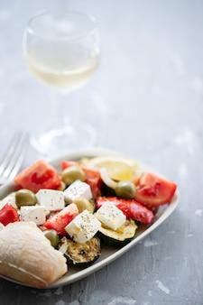 Salat mit frischem und gegrilltem gemüse auf weißem teller auf grauer keramik