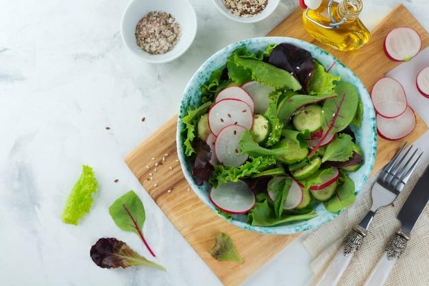Salat mit frischen radieschen, rucola, rüben, mangold, sonnenblumenkernen, leinsamen und sesam auf einer hellen oberfläche. selektiver fokus. draufsicht. speicherplatz kopieren.