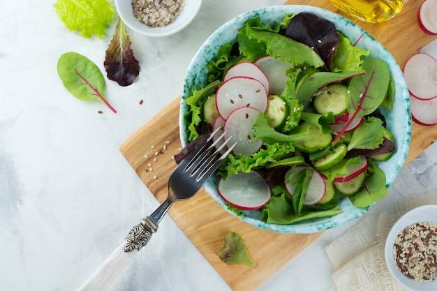 Salat mit frischen radieschen, rucola, rüben, mangold, sonnenblumenkernen, leinsamen und sesam auf einer hellen oberfläche